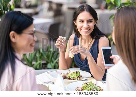 Happy lady speaking with beaming affiliates while eating dish in cafe. She sitting at table
