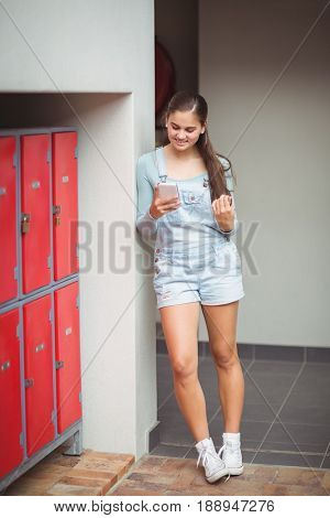 Schoolgirl using mobile phone in locker room at school