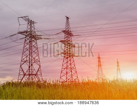 Landscape with high-voltage power lines. Electricity distribution station. High voltage electric transmission tower at sunset.