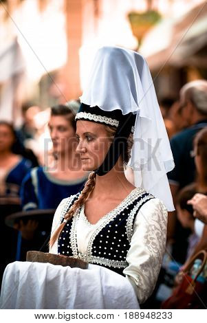 Asti, Italy - September 19, 2010: Young Medieval Princess, during the historic parade of the Palio of Asti in Piedmont, Italy. Young damadel Middle Ages at the Palio with flowers