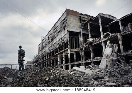 Soldier in military uniform stands on the ruins of the destroyed house. Hot spots on the planet. The concept of the fight against terrorism.