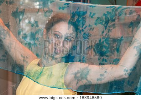 Young 20S Girl Looks At The Camera Through Transparent Silk Neckerchief  That She Holds In Her Hands
