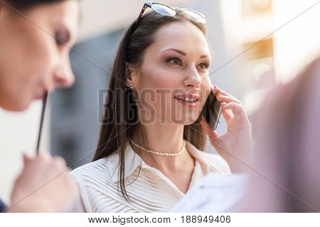 Low angle female demonstrating happiness while speaking by phone in cafe. Her friends are sitting near her