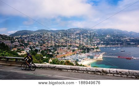Nice France - June 8 2006: Cyclist rides along popular road with scenic view of the city and harbor in Nice France.