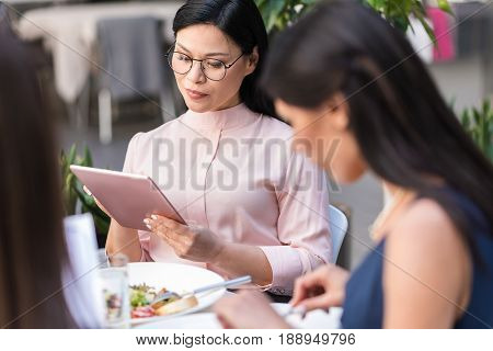 Serene asian businesswoman looking at electronic tablet while locating at desk in confectionary shop