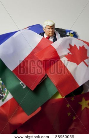 Caricature of United States President Donald Trump buried in a pile of world flags - overwhelmed - global issues concept - action figure toy