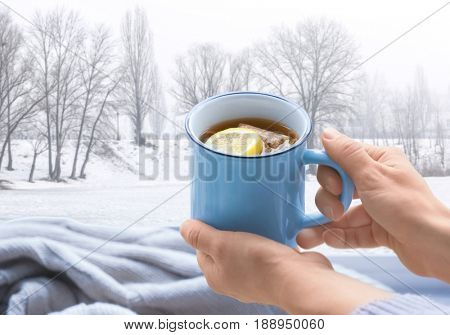 Woman holding cup of aromatic tea. View of snowy forest from window