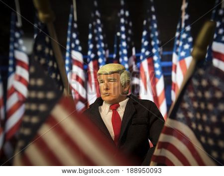 Caricature of United States President Donald Trump standing among US Flags - election concept - patriotism - Make America Great Again concept - action figure toy