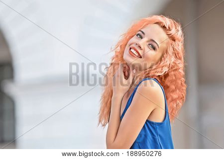 Trendy hairstyle ideas. Young woman with dyed apricot hair outdoor