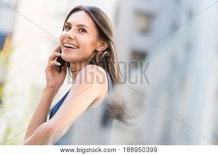 Low angle youth female demonstrating happiness while speaking by phone outdoor