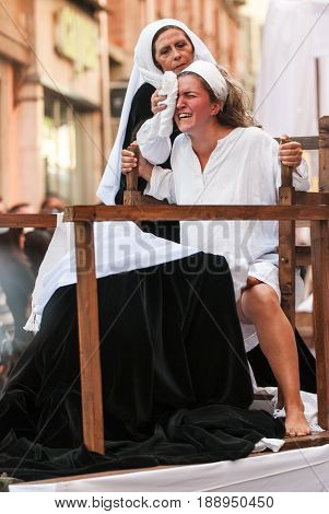 Asti, Italy - September 19, 2010: Historical representation of woman while giving birth during the historic parade of the Palio of Asti in Piedmont, Italy. The parade consists of more than 2000 dressed in medieval clothes.