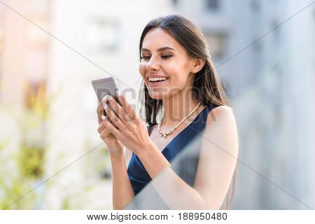 Lady expressing gladness while writing message by mobile on street