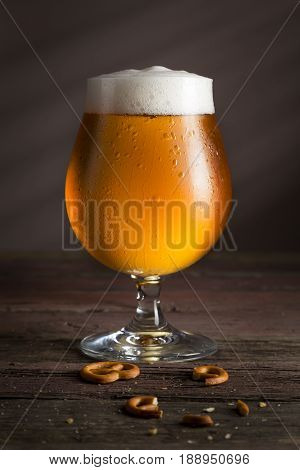Glass of cold light unfiltered beer on a rustic wooden table. Selective focus