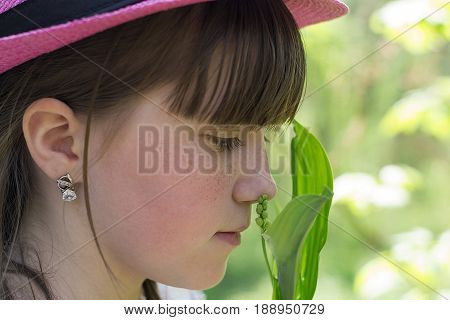 A portrait of a small beautiful baby girl in a pink summer hat which she brought to the flower's face and with a pensive look sniffs it
