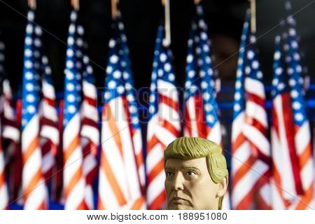 Caricature of United States President Donald Trump  - Head above water concept - using a bobble head figure with US Flag backdrop