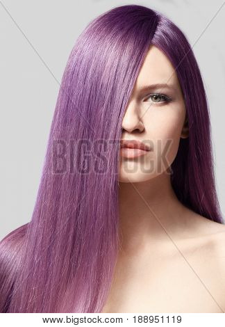 Lilac color for trendy hairstyle ideas. Young woman with dyed hair on light background