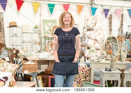 A Female Stall Holder Standing In Front Of Vintage Crafts