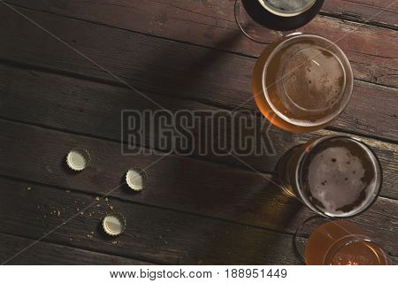 Top view of pale dark unfiltered pale and red fruit beer in four different beer glasses on a rustic wooden table. Focus on the table and beer corks