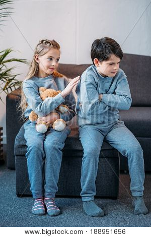 Adorable Girl Holding Teddy Bear While Offended Boy Sitting On Sofa At Home