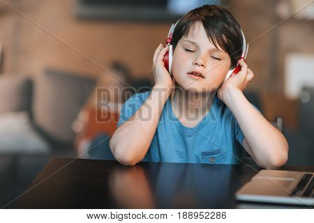 Kid Boy Listening Music In Headphones While Sitting At Home