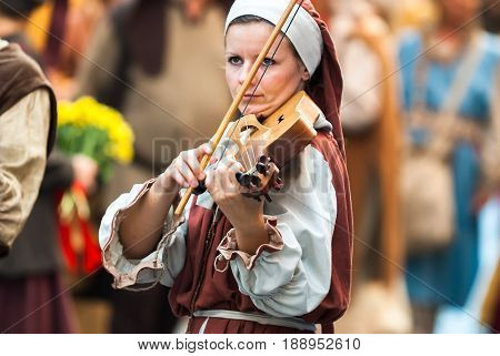 Asti, Italy - September 18, 2011: the historic Medieval parade of the Palio of Asti in Piedmont, Italy. young woman of the Middle Ages plays a musical instrument similar to the violin