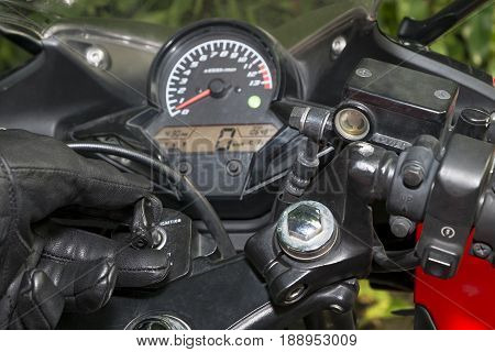 Biker in the black leather glove inserting key to starting the motorcycle engine. sport motorcycle ignition scence.