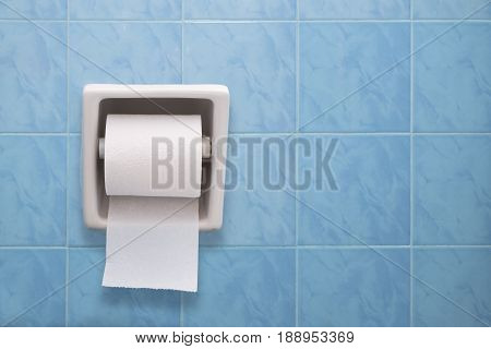 Tissue paper roll in bathroom clean toilet paper on clean blue mosaic background.