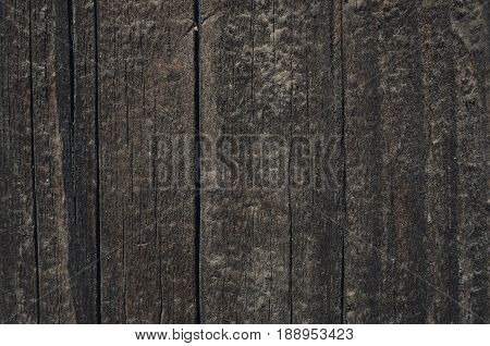 Dark vertical boards made of wood. Vertical lines of a wall from a natural tree