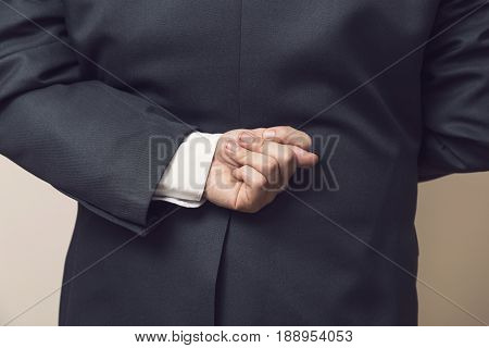 Close up of a businessman in a suit holding fingers crossed behind his back while making false promises