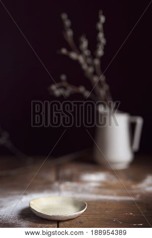 Rustic plate placed on a wooden table sprinkled with flour with a flower vase in the background. Selective focus on the plate