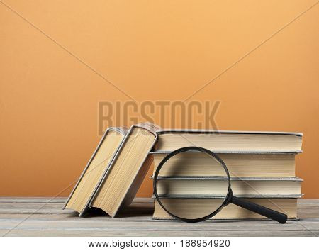 Stack of books on wooden table on colorful wall background and loup.
