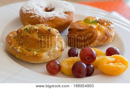 Danish pastry and fruits on white dishclose-up.
