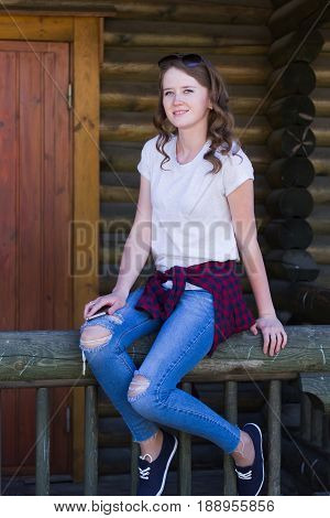 A young girl with a phone in her hand in jeans a T-shirt and a red checkered shirt strapped to her belt sitting on the railing of a wooden house looks away with a smile