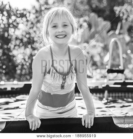 Fun weekend alfresco. smiling active child in colorful swimsuit playing in the swimming pool