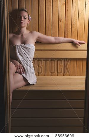 Beautiful young woman relaxing and enjoying a finnish sauna session