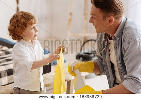 It is for you. Little son standing in semi position and holding duster in both hands while looking into eyes of his father