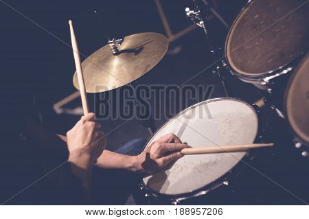 Close up of hands of male drummer holdning drumsticks sitting and playing drums in studio