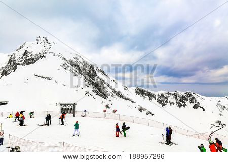 Winter landscape. Snow covered high mountain peaks under cloudy panoramic skies in Europe. People engage winter extreme sports. Downhill skiers and snowboarders. Krasnaya polyana, Sochi, Russia.