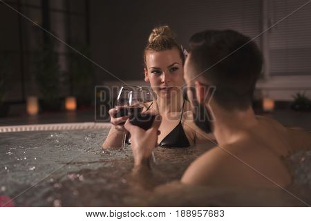 Young couple in love enjoying romantic wellness spa weekend making a toast with glasses of wine in a jacuzzi bath tub