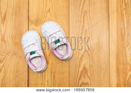 a pair of baby sneakers on wood background very cute of used baby shoes.