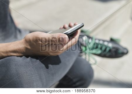 closeup of a young caucasian man outdoors wearing quad roller skates using his smartphone