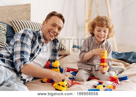 Always smile. Handsome father keeping smile on his face while looking straight at camera and holding parts from meccano