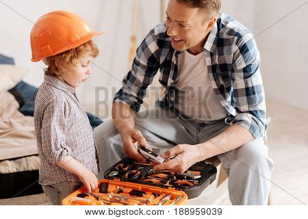 Listening to father. Smiling man sitting on the bench and holding instrument while looking at his son