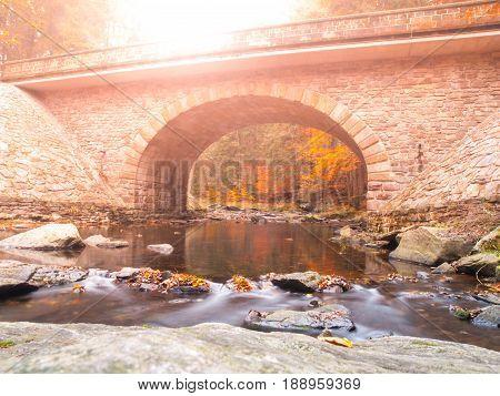 Stone bridge over River Divoka Orlice at Zemska brana, Orlicke hory, or Eagle Mountains, Czech Republic. Autumn time.
