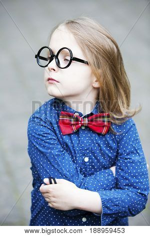 funny portrait of blond boy in shirt and bowtie with huge glasses looking arrogant