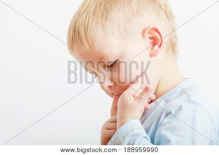 Tasty yummy food for children concept. Boy licking something good from fingers.