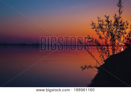 Beautiful colorful dusk on a river. Silhouettes of reeds on near bank and trees on far bank.