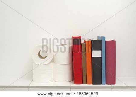 Read books in the bathroom, colorful books and toilet paper on the white tiled shelf