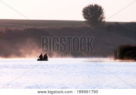 Fishermens in fishing boat at sunrise in summer on lake in foggy weather