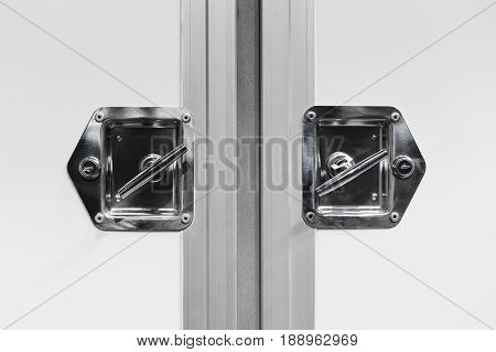 Closed doors of cargo truck, handle and lock of delivery vehicle with white bodywork, commercial transport industry, detail